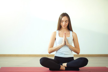 Young attractive woman practicing yoga, sitting in Padmasana, exercise, Lotus pose, namaste