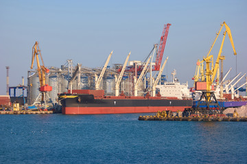 Freight ship near sea port. Industrial port where freight loads are carried for national and international shipping.