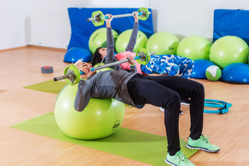Girls in tracksuits lying on fitness balls doing barbell chest press in a gym. Two young women exercising indoors.