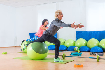 Active middle-aged woman working out with stability ball taking part in group fitness class
