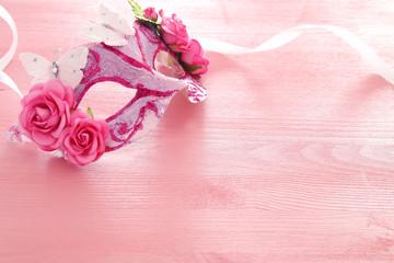 Image of delicate elegant venetian mask over wooden pink background. Selective focus.
