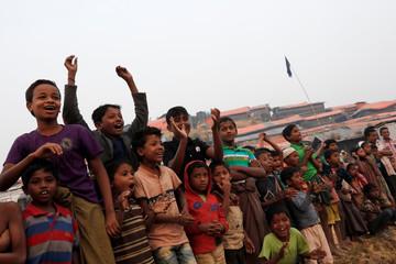 Rohingya refugee children react as they watch a football match in Palong Khali camp, near Cox's Bazar,