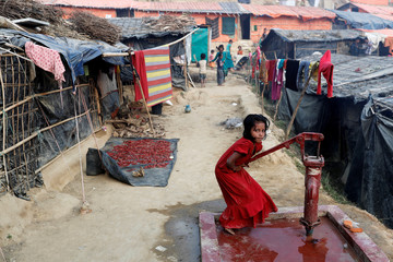 A Rohingya refugee girl plays at a tube-well in Palong Khali camp, near Cox's Bazar