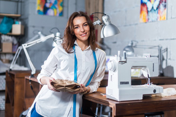 Portrait of smiling European fashion designer standing next to sewing machine holding a gift packed in craft paper in studio