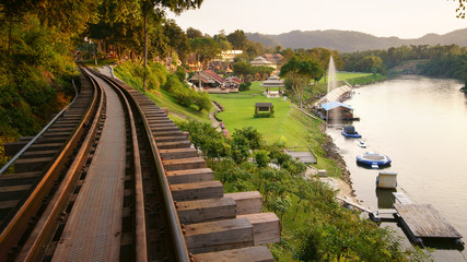 nature landscape railroad tracks and fountain on river with green grass meadow in the resort or hotel for tourist travel on relax holiday with warm sunlight at kanchanaburi in Thailand