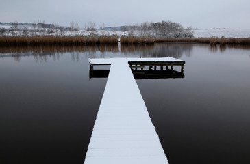 Snow covered pier is seen on a lake near the village of Etyek