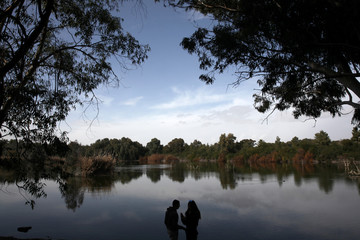A couple stands on a lake shore in Nicosia