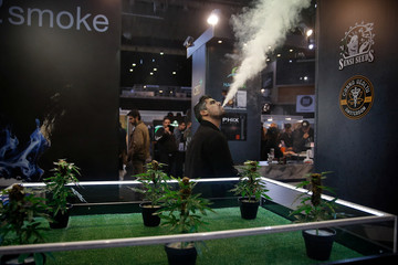 A visitor uses an electronic cigarette during the 1st International Cannabis Expo, in Athens