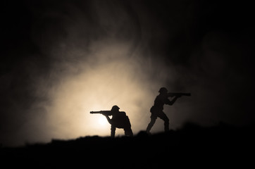 Military silhouettes of soldiers against the backdrop of dark foggy sky. Battle scene with explosion and burning clouds behind fighing soldiers. Toy decoration
