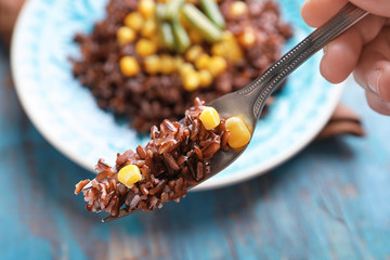 Hand holding fork with red rice and corn, closeup
