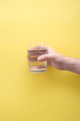 Hand holding a glass full of water on yellow background