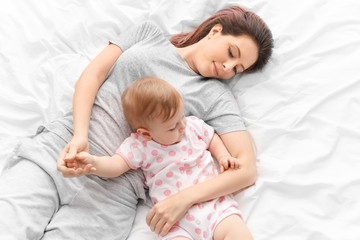 Young mother with her cute baby on bed