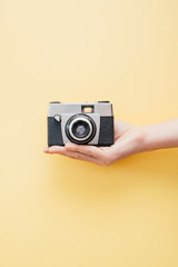 Hand holding vintage style camera on yellow background