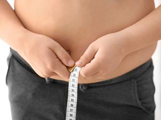Overweight boy measuring his waist, closeup