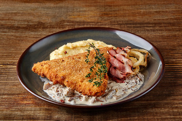 Chicken schnitzel with herb, mashed potatoes and mushrooms sauce on plate on wooden table background. Healthy food.