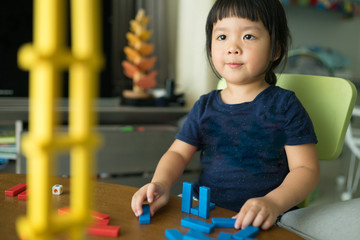 Little girl playing with wooden blocks the unstable tower.Building collapse games.Children imagination or creativity concept.Little asian girl playing with colorful toy blocks.