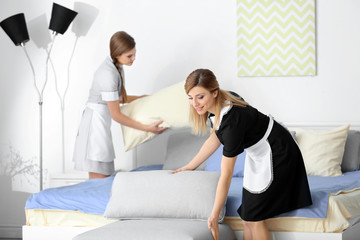 Young chambermaid in uniform working indoors