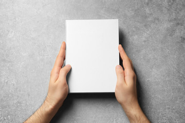 Man holding book with blank cover on grey background. Mock up for design
