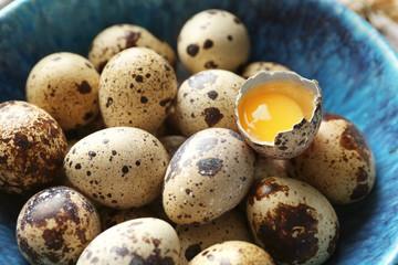 Raw quail eggs in bowl, closeup