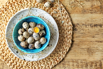 Raw quail eggs in bowl on wooden table