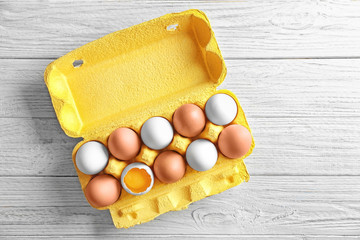Raw chicken eggs in package on wooden table