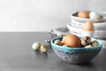 Bowl with quail and chicken eggs on table