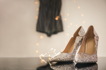 Pair of sparkly female shoes on blurred background