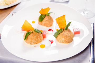 Plum dumplings with cinnamon, white chocolate and vanilla sauce served in a restaurant