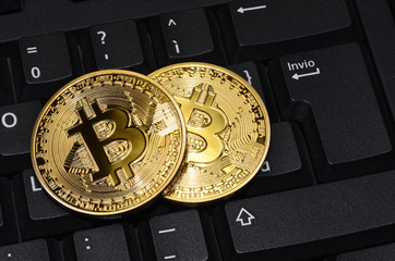 close up of cryptocurrency phisical bitcoin over computer keyboard. concept business image
