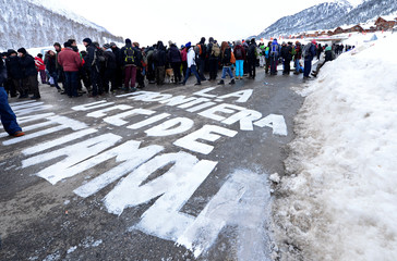 "A writing reading ""The border kills: destroy it"" is seen on the road as demonstrators march from Claviere in Italy to Montgenevre in France to ask for open borders for migrants"