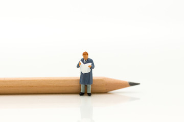 Miniature people, businessman reading book with the pencil. Image use for background education,or business concept.