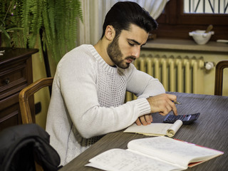 Handsome young man using calculator and accounting at table or studying math