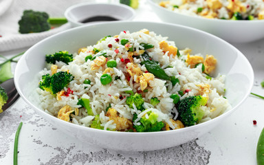 Fried rice with vegetables, broccoli, peas and eggs in a white bowl. healthy food