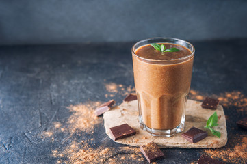 Chocolate smoothie with banana, decorated with mint leaf on the dark background with pieces of chocolate and cocoa powder. Healthy diet food. Selective focus, space for text.