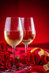 Valentines or wedding concept. Wine cups red roses and romantic setting for two in red. Greeting card for jubilee or aniversary