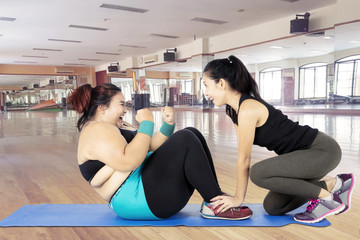 Overweight woman doing sit ups with her trainer