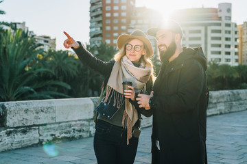 Sunny day. A loving couple of young tourists, friends are walking along the city street, drinking coffee. The girl is pointing at something. Vacation, travel, adventure, lifestyle. Backlight.