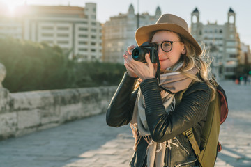 Sunny day, autumn. Young woman tourist, photographer, hipster girl dressed in hat and eyeglasses, stands on city street and takes photo. Vacation, travel, adventure, sightseeing. Blurred background.