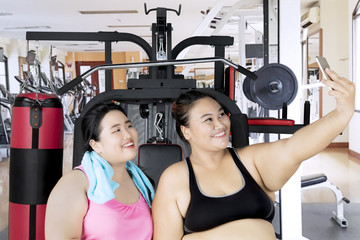 Obese women with smartphone in gym center