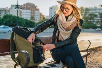 Young woman tourist, a hipster girl with camera, dressed in hat and eyeglasses, sits on bench in city street,is looking for something in her backpack. Vacation, travel, adventure.Blurred background.