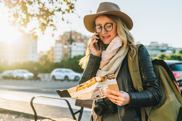 Young woman tourist with backpack,dressed in hat and glasses,sits on bench in city street, looks at map and talks on her cell phone.In background,in soft focus, road and car.Hipster girl using gadget.