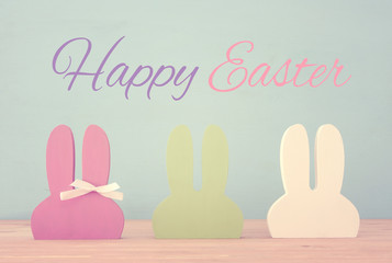 Cute colorful wooden bunny ears over background.