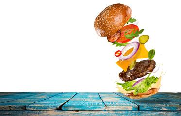 Big tasty burger with flying ingredients.