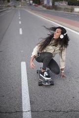 Young girl having fun in the street with longboard