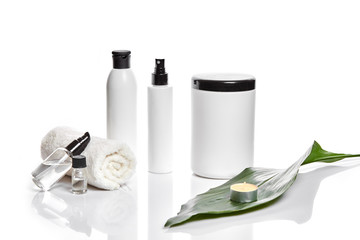 Set of cosmetic products in white containers on light background.