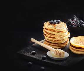 Stack of pancakes with fresh berries served on old black board . Selective focus.