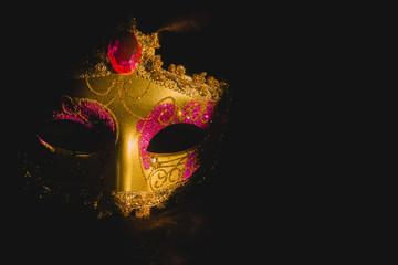 Golden venetian mask on a black background