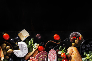 Italian food ingredients ham, salami, tomino, various olives, bread on black wooden board, copy space.