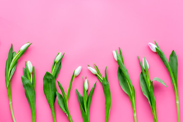 Pale pink spring tulips on pastel pink background top view copy space