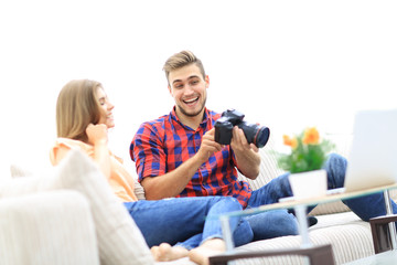 young man shows a photo of his girlfriend sitting in the living room
